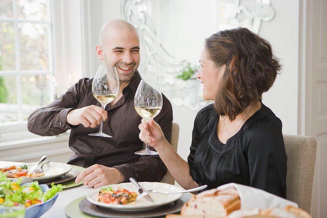 Man and woman raising glasses of wine