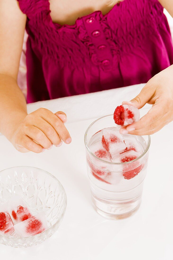Girl holding a raspberry ice cube in her hand