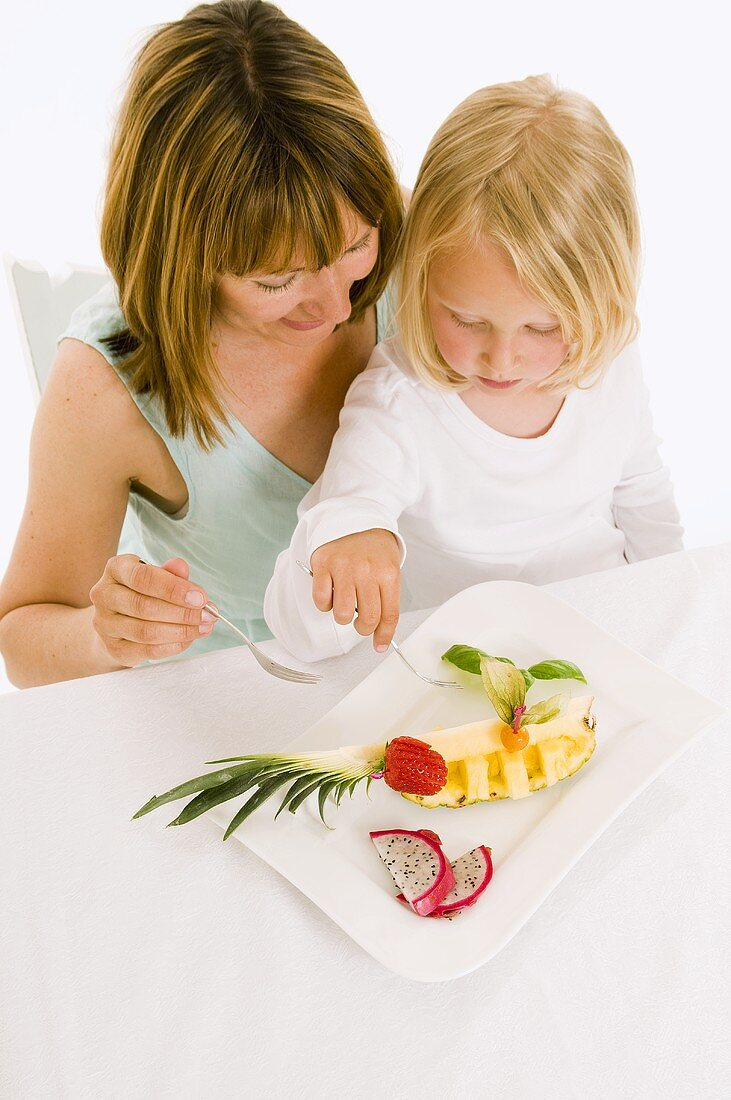 Mother and daughter eating fruit from plate
