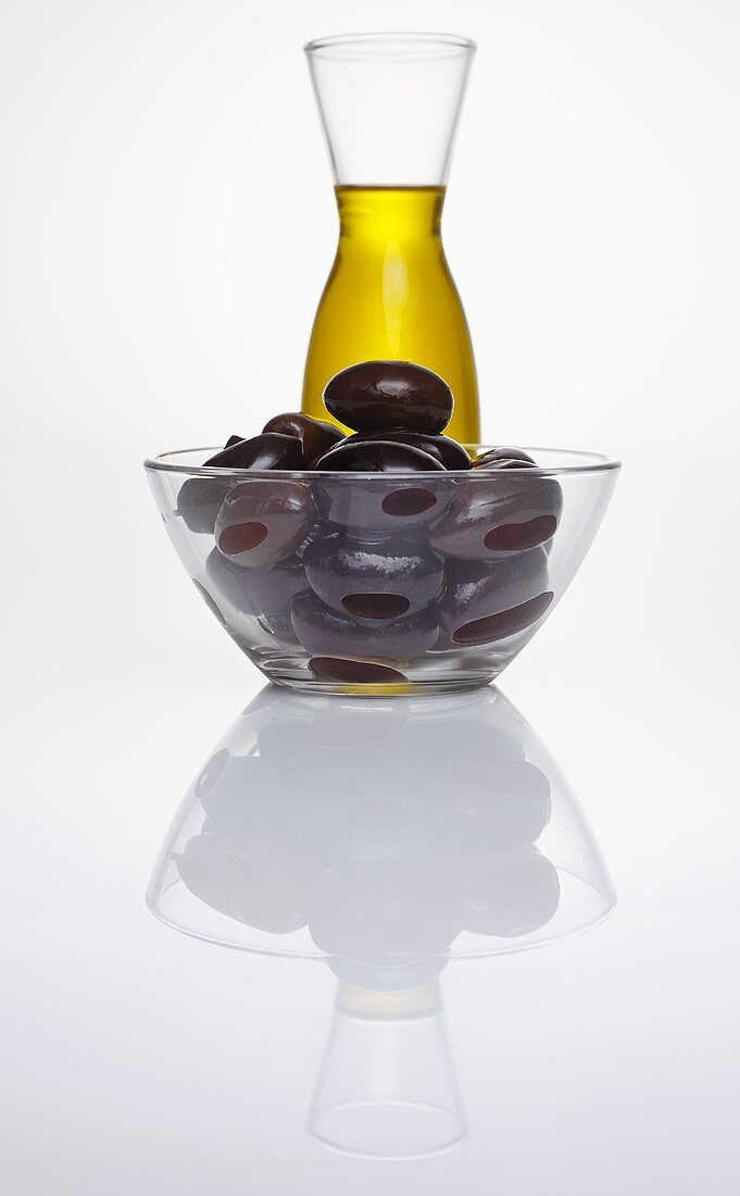 Black olives in glass dish in front of carafe of olive oil