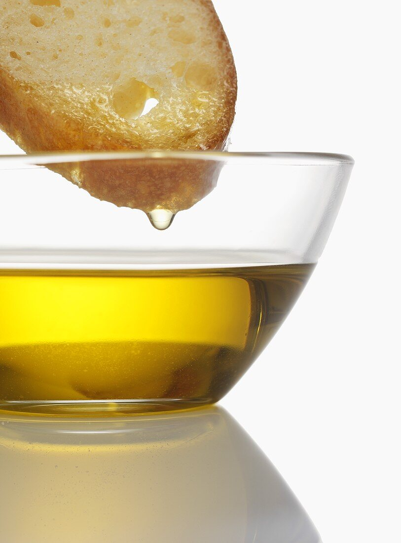 Olive oil dripping from slice of bread