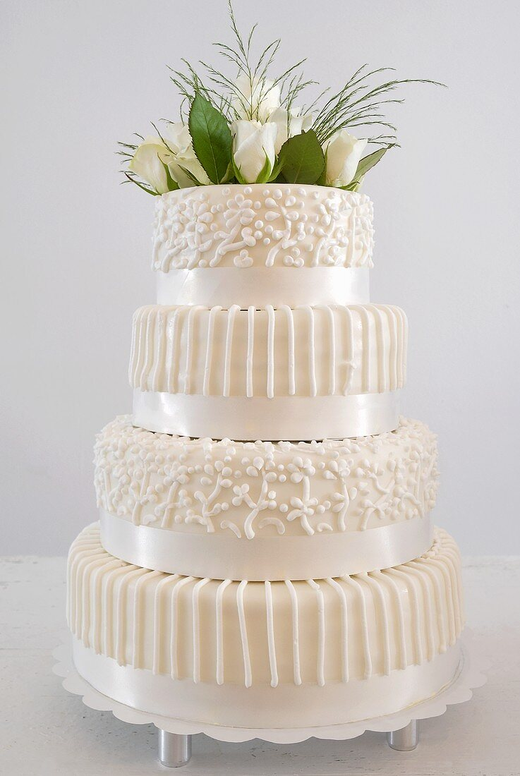 Four-tiered white wedding cake with floral decoration