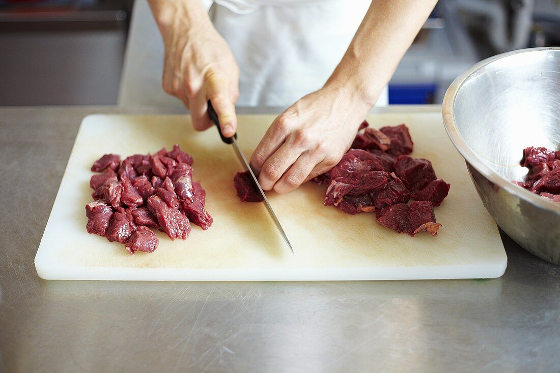 Chef cutting up beef