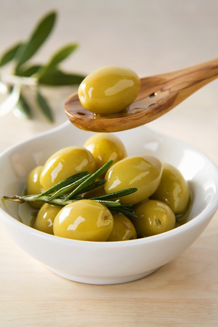 Green olives in small dish and on wooden spoon