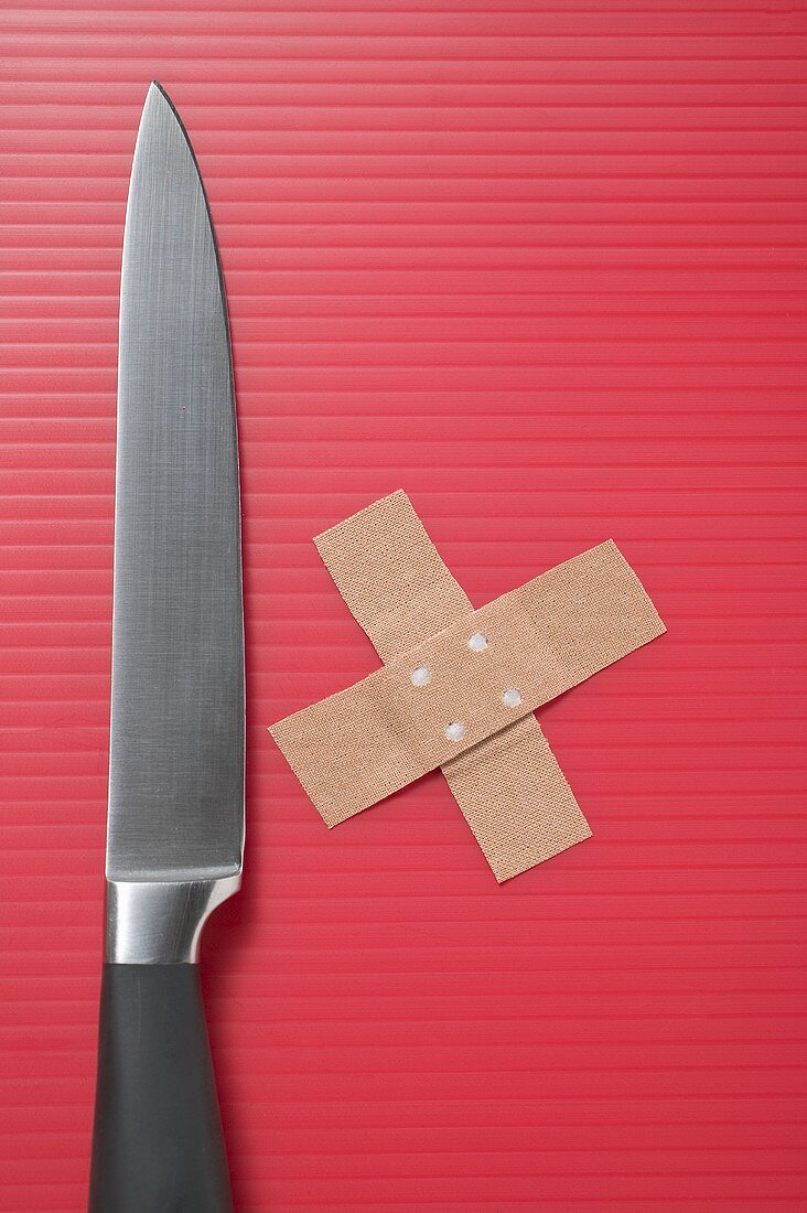 Knife and crossed sticking plasters on red background