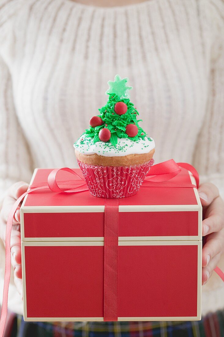 Woman holding cupcake on Christmas parcel