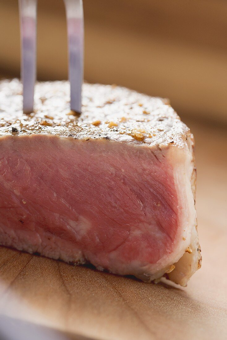 Sirloin strip steak with carving fork