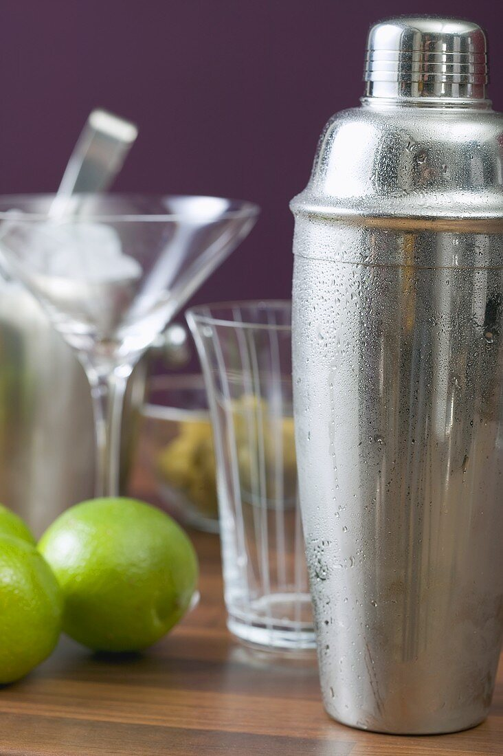 Cocktail shaker, glasses and limes
