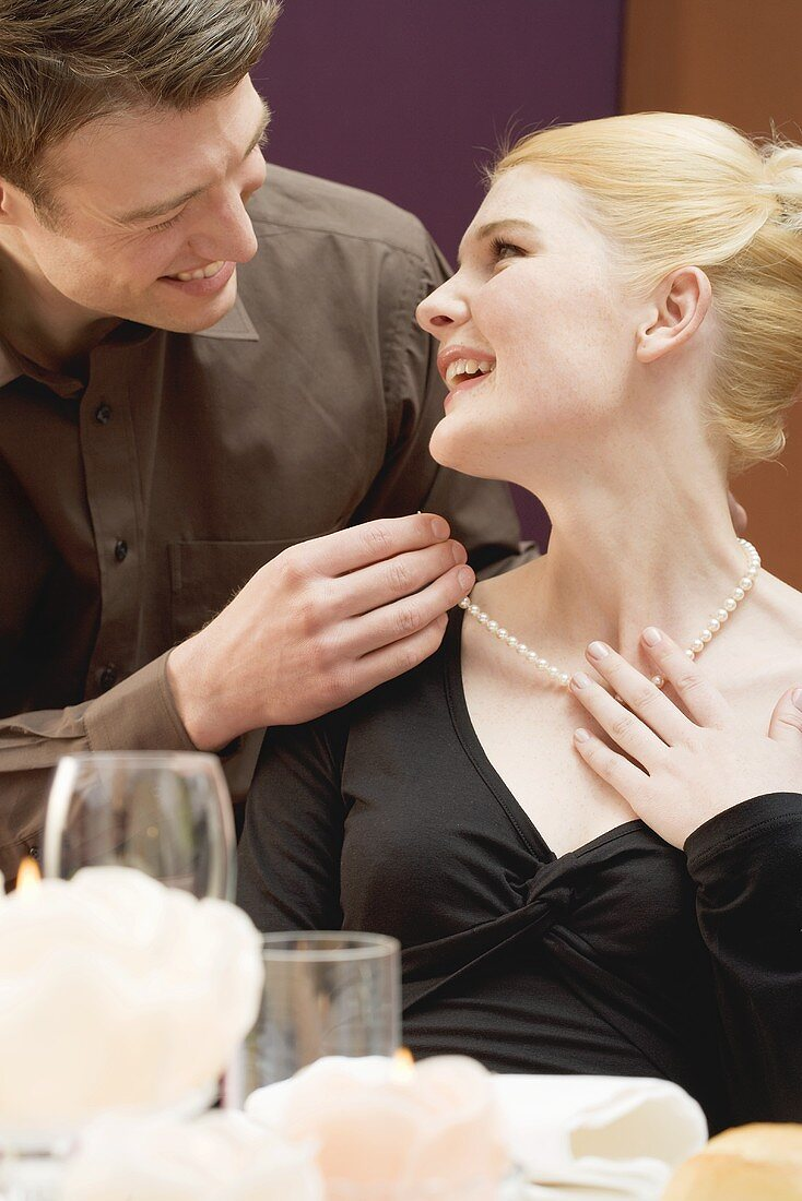 Man putting pearl necklace around woman's neck