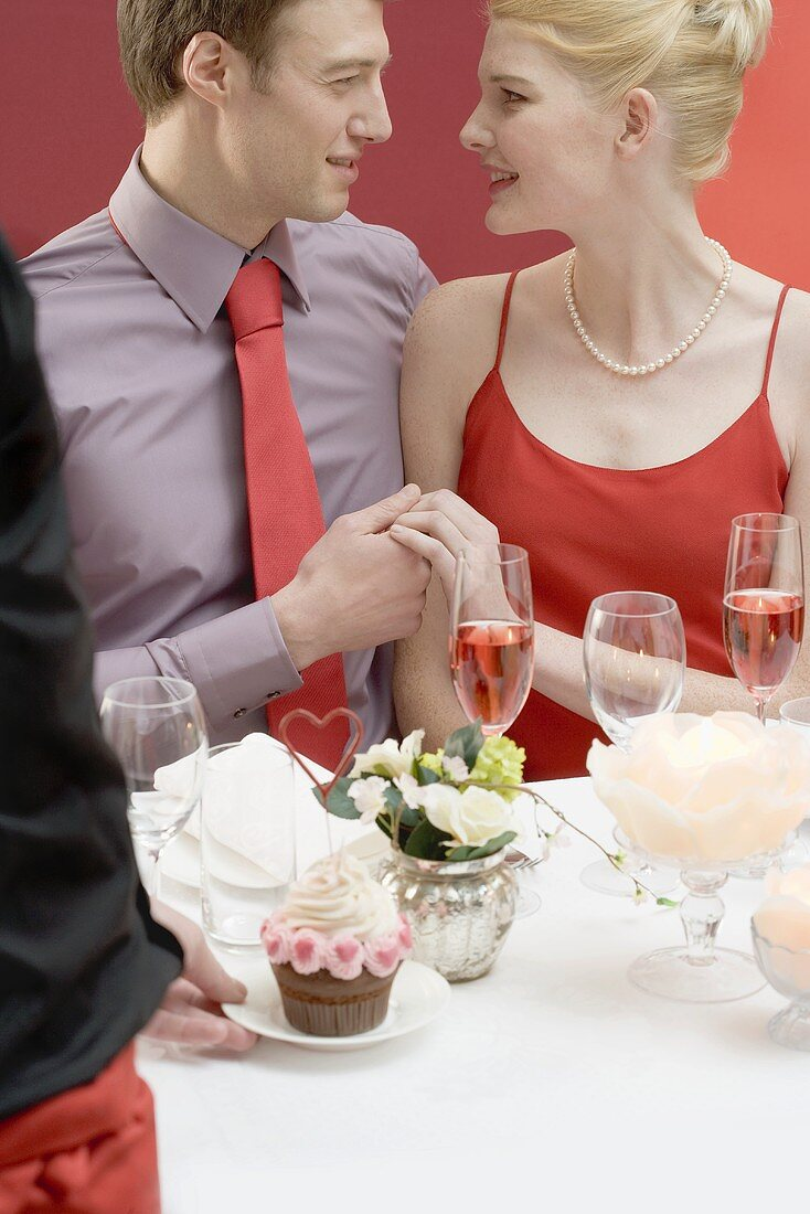 Waiter serving cupcake with hearts to romantic couple