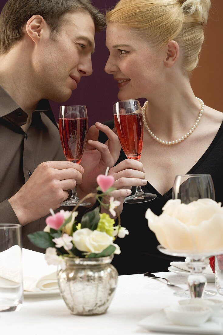 Couple with glasses of sparkling wine at laid table
