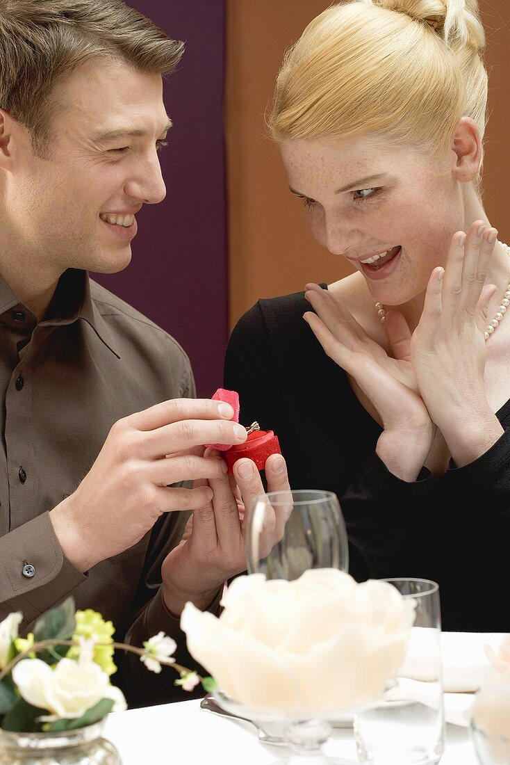 Man giving woman diamond ring over romantic meal