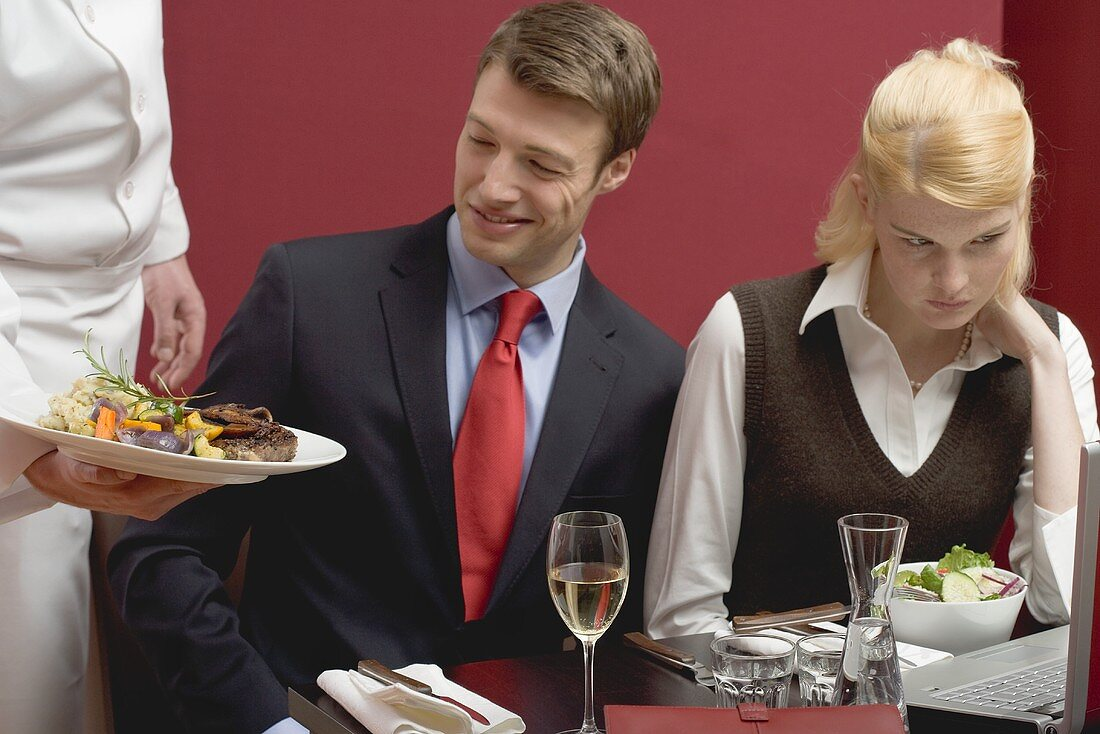 Waiter serving lunch to business people