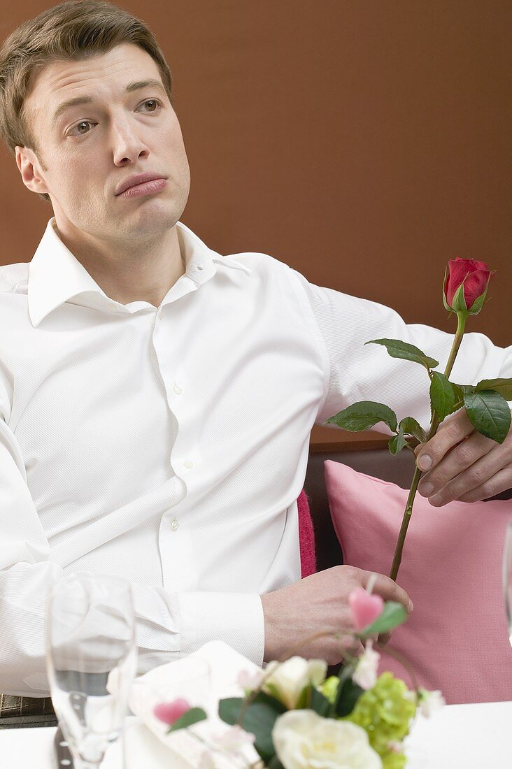 Lonely man with red rose in restaurant