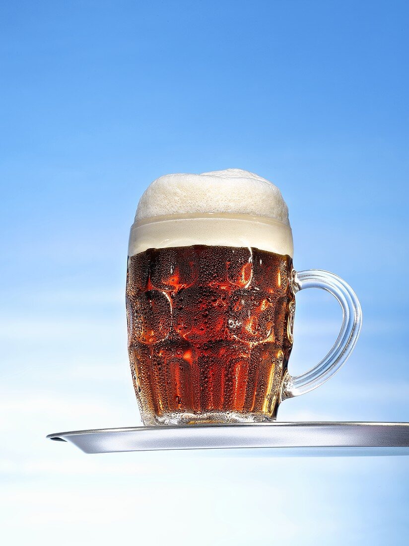 Altbier (top-fermented beer) in glass mug on tray