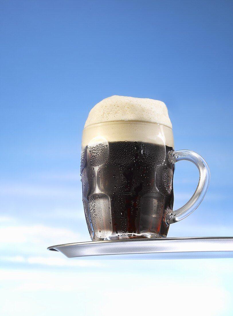 Dark beer in glass mug on tray