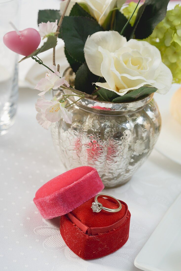 Flowers and engagement ring at a romantic dinner