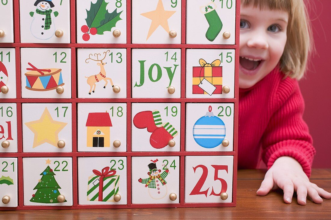 Small girl peeping out from behind Advent calendar