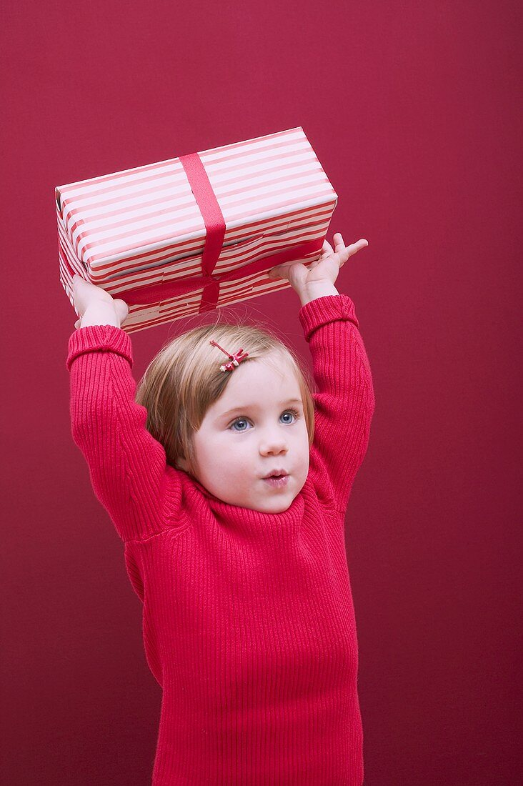 Small girl holding Christmas parcel