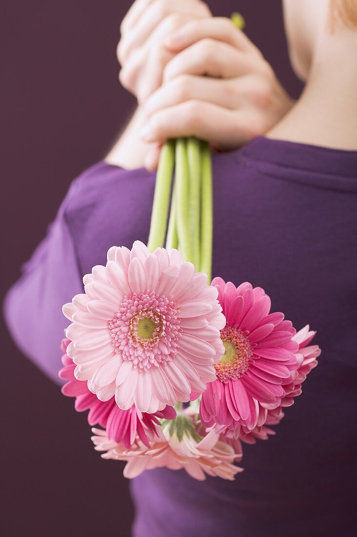 Woman holding bunch of flowers over her shoulder