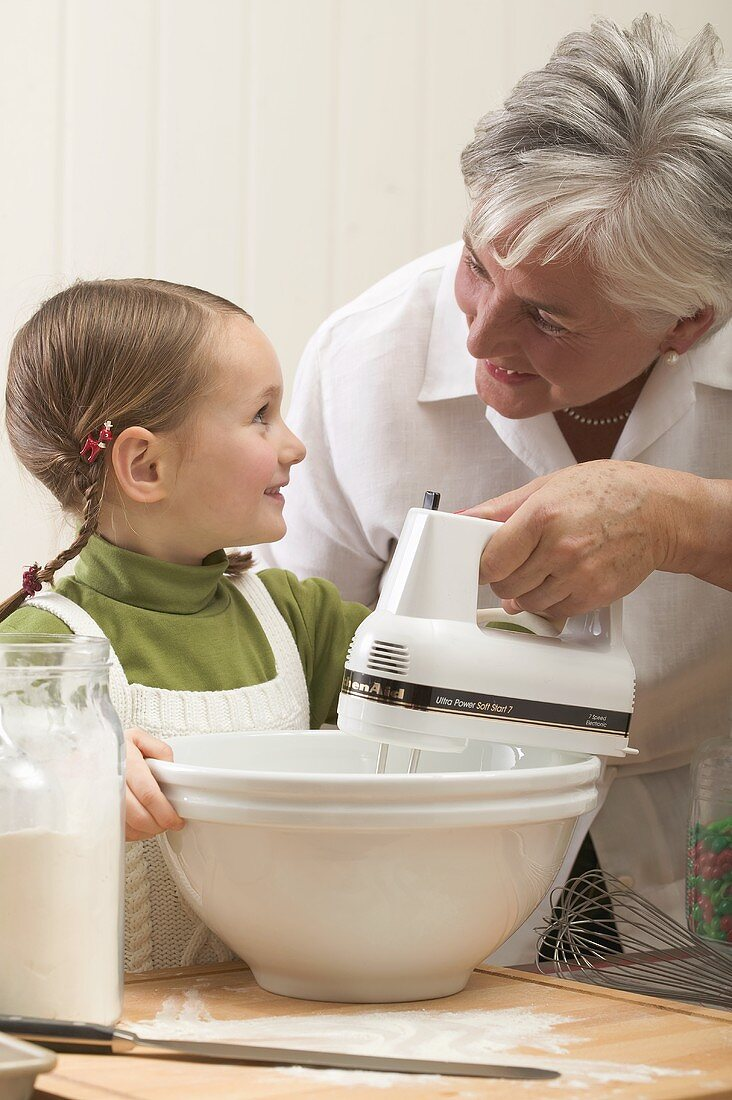 Grandmother showing granddaughter how to use electric mixer