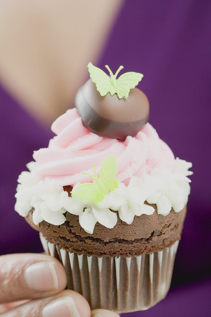 Woman holding a chocolate cupcake with butterflies