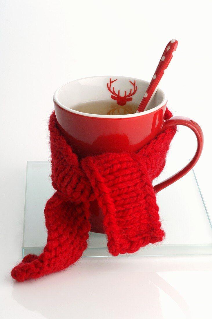 Festive mug of tea with knitted scarf