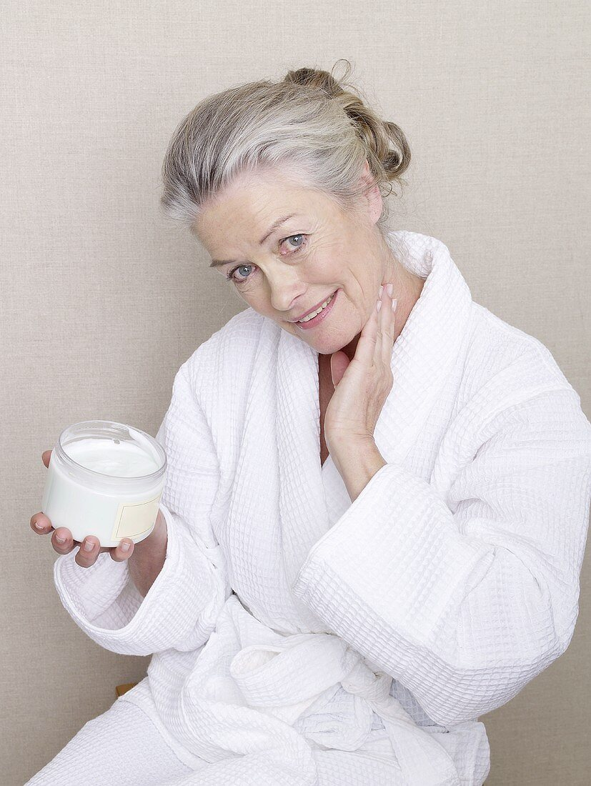 Mature woman in bathrobe creaming her neck
