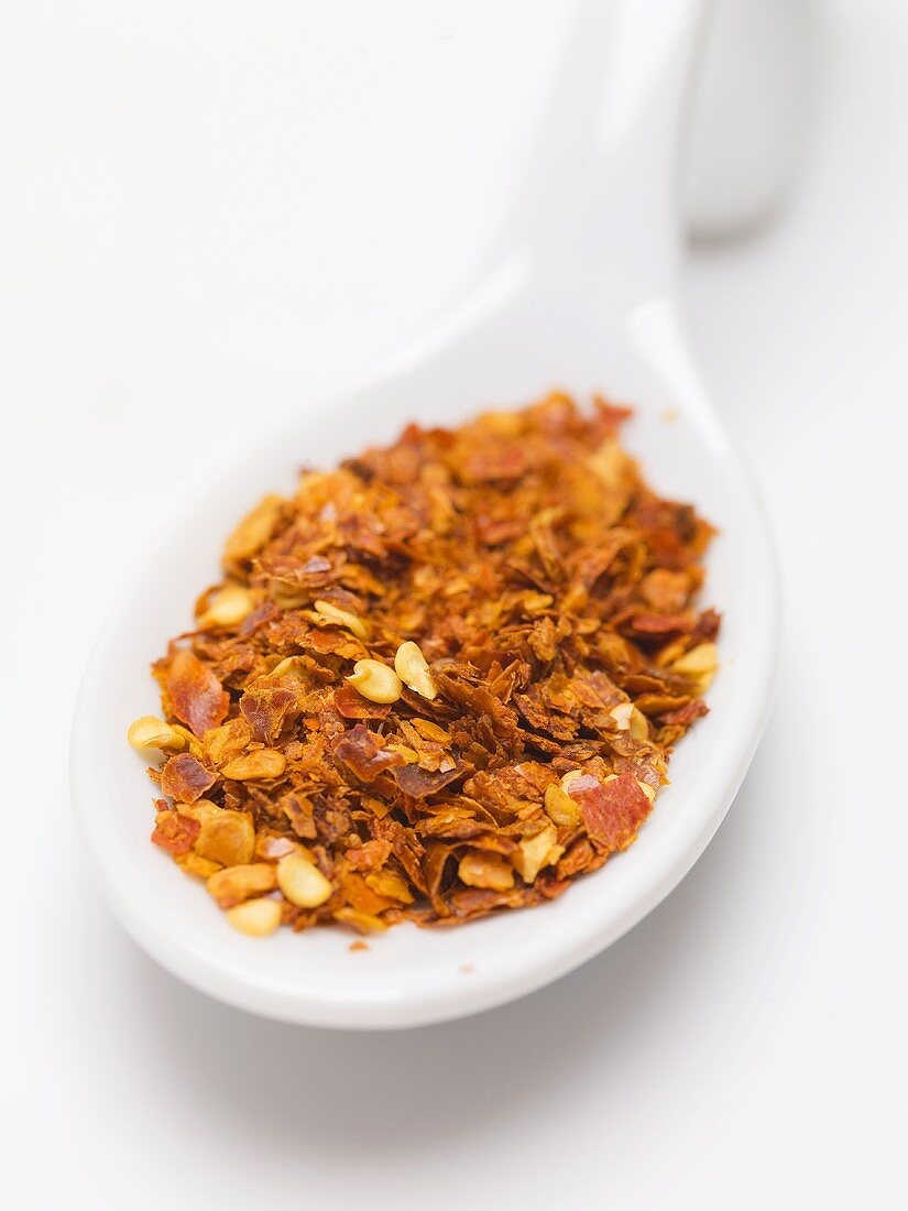 Chilli flakes on spoon (close-up)
