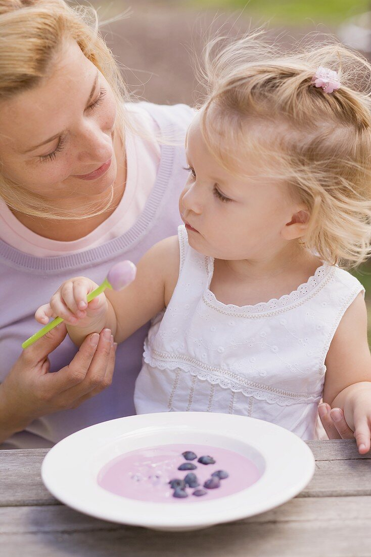 Mother and young daughter with a dish of blueberry yoghurt