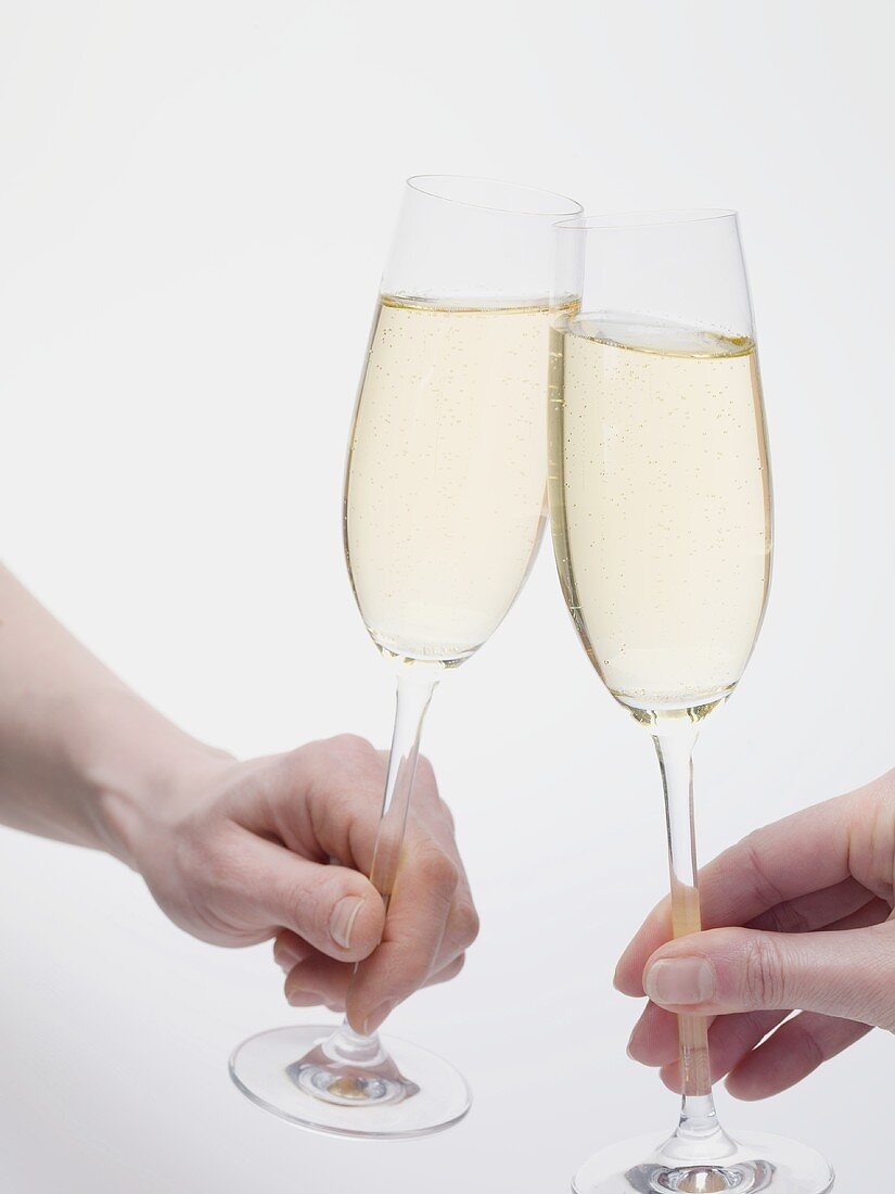 Hands clinking glasses of sparkling wine