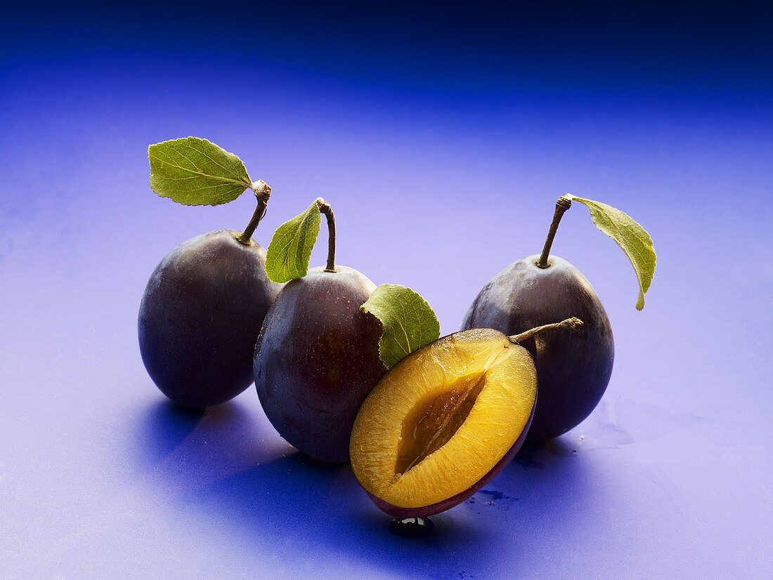 Three whole plums and half a plum with leaves