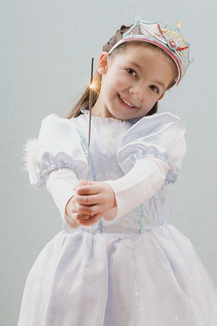 Little girl dressed as princess holding a sparkler