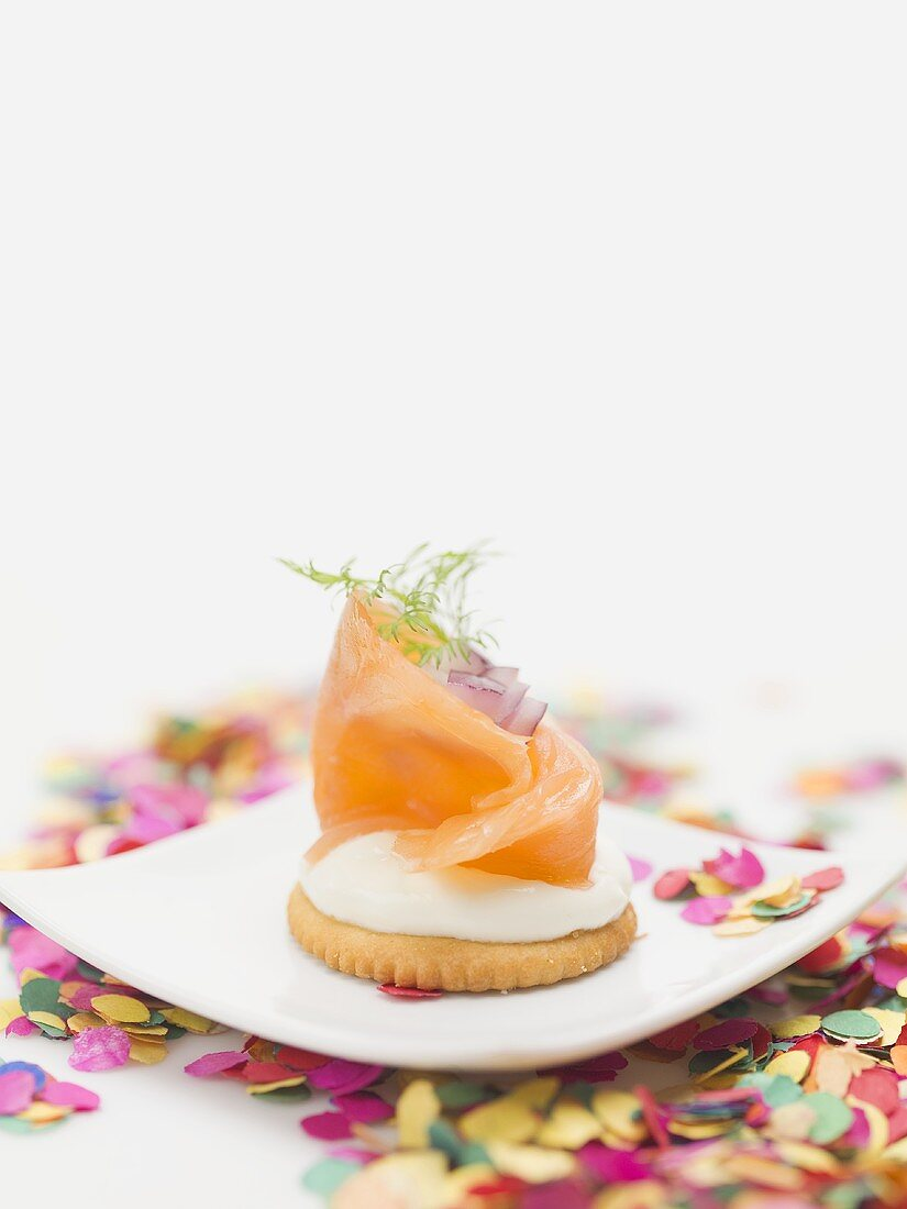 Smoked salmon on cracker on plate surrounded by confetti