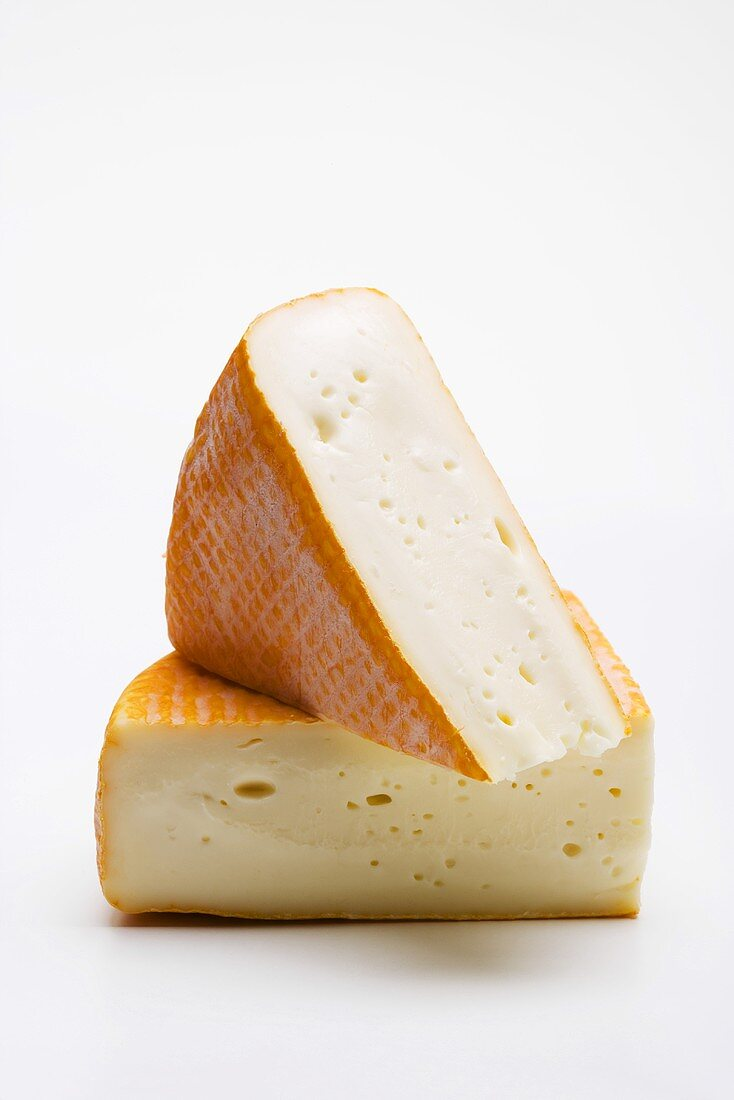 Two pieces of washed-rind cheese
