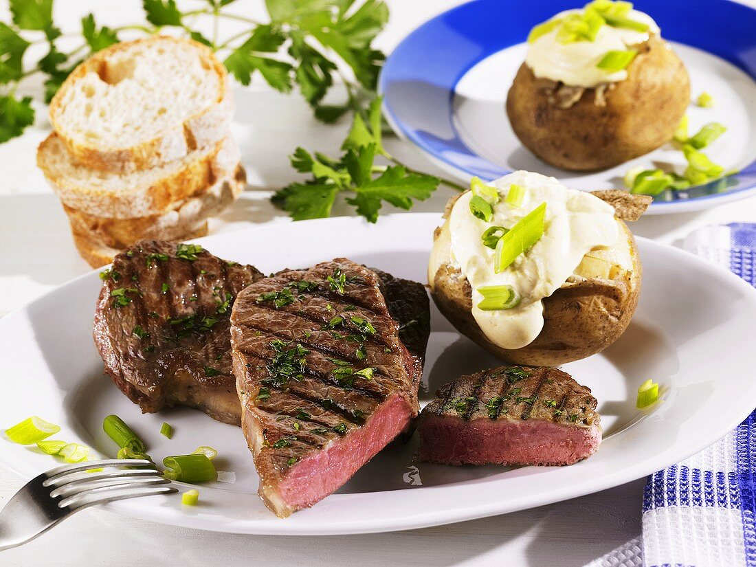 Grilled rump steak with baked potato and sour cream