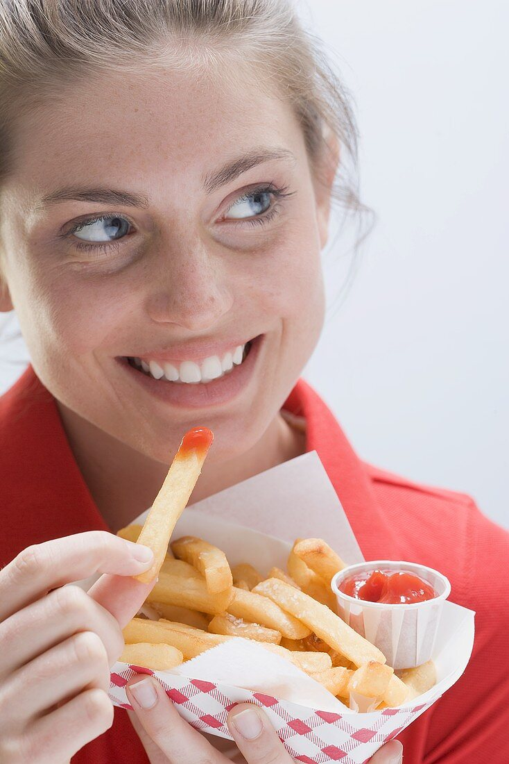 A smiling woman eating a bag of chips