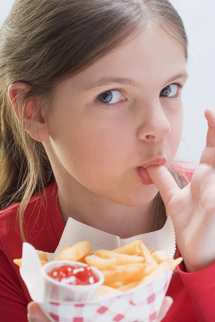 A girl eating chips, licking her thumb