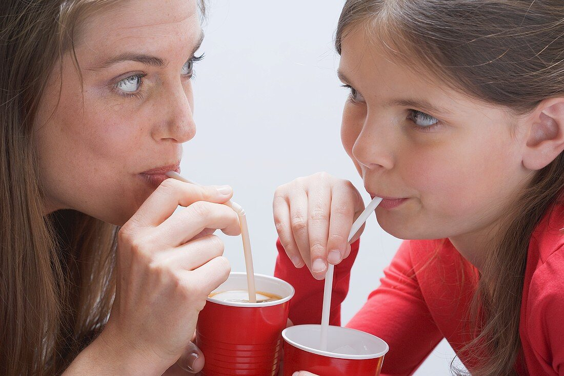 Girl and young woman drinking milkshakes