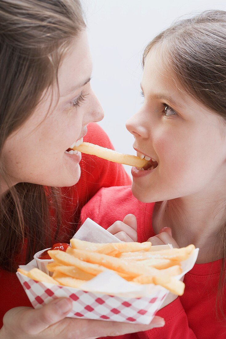 Young woman and girl eating the same chip