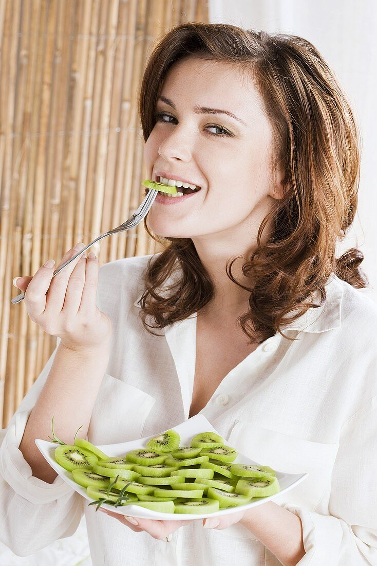Young woman eating kiwi fruit