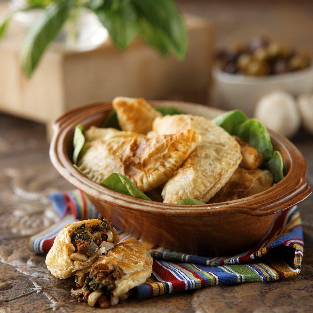 Empanadas Served in a Ceramic Crock; One Broken in Half