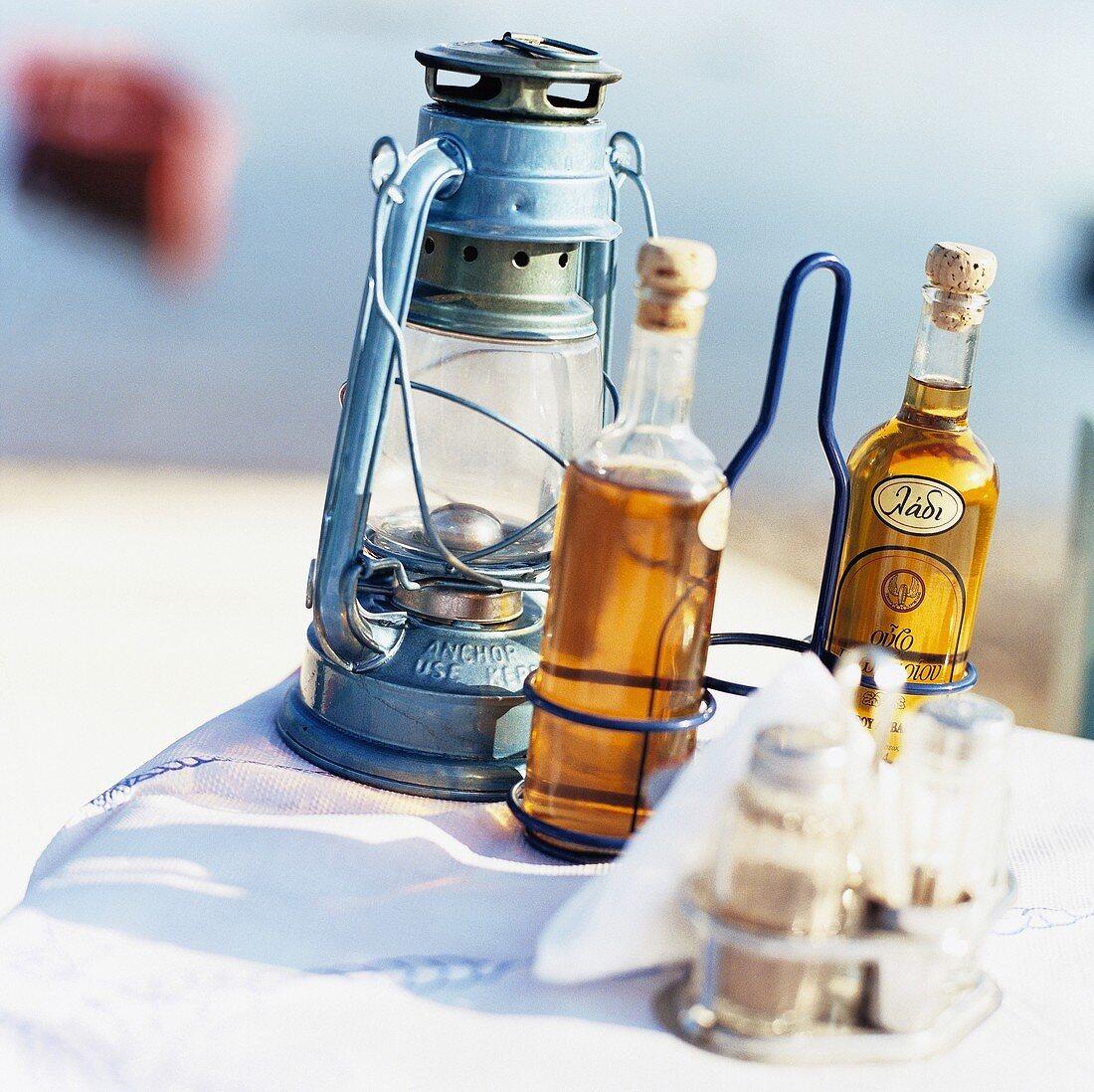 Cruet stand, oil, vinegar & hurricane lamp on table out of doors