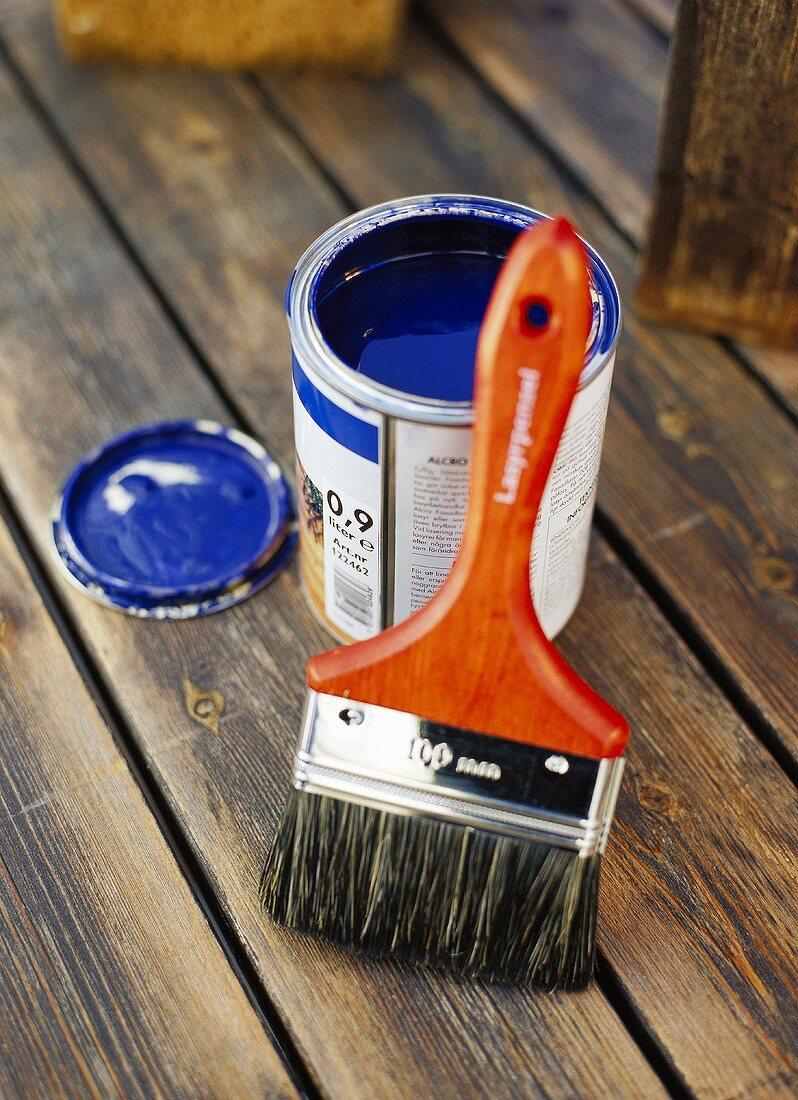 Blaue Farbe mit Pinsel auf einem Holzboden