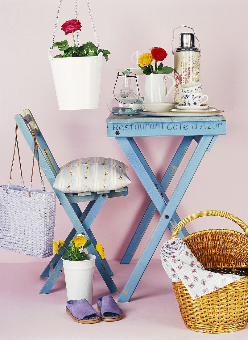 Blue table with crockery, chair, basket and flowers