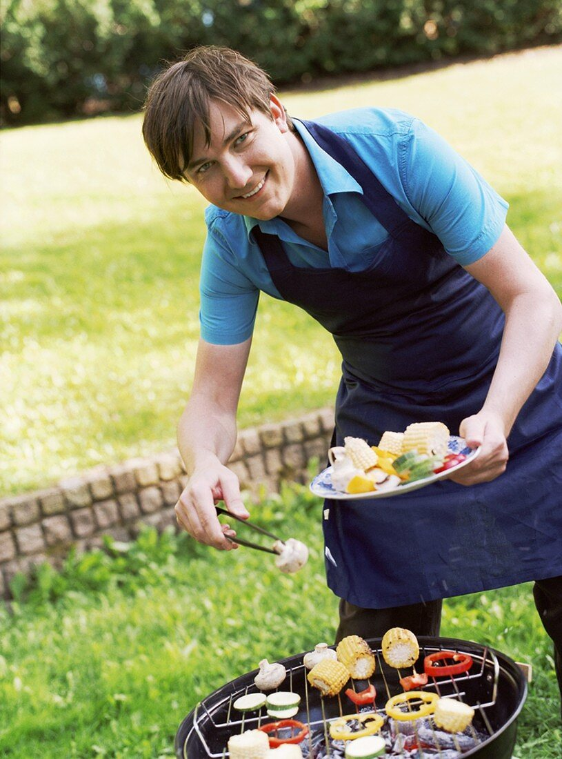 Young man barbecuing food