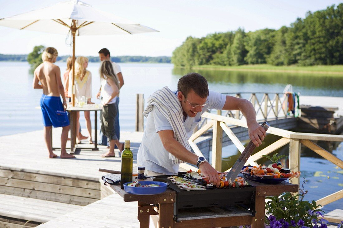 Man barbecuing food, young people on landing stage in background