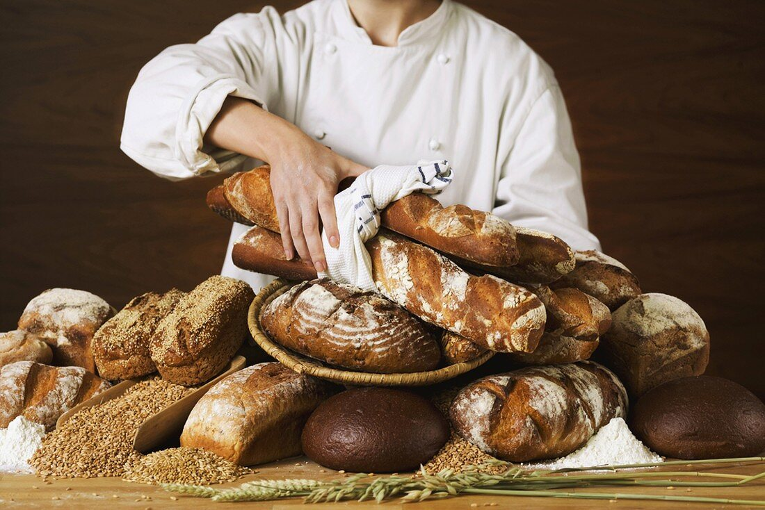Baker with various loaves of bread