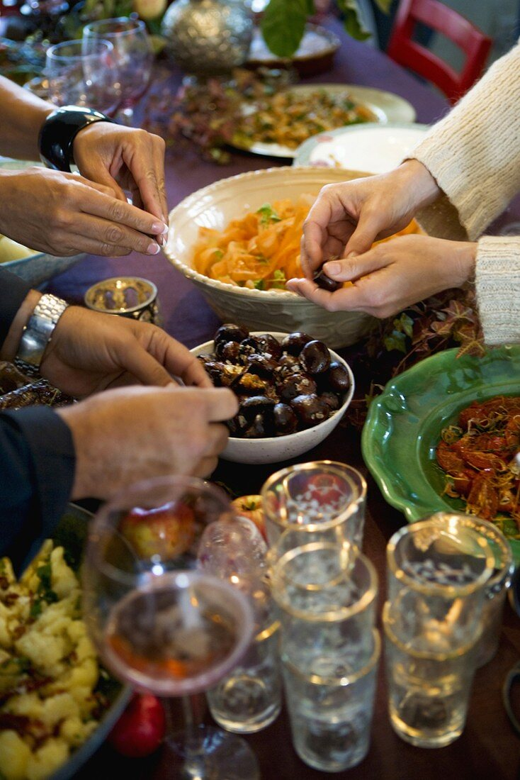 Hands reaching for appetisers