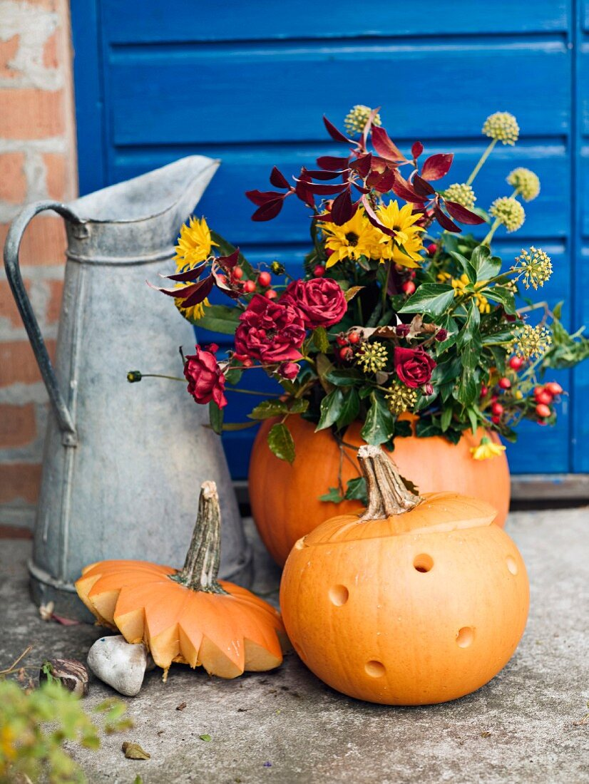 Metal jug, pumpkins and flower arrangement in front of house